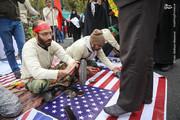 عکس | واکس زدن کفش راهپیمایان روی پرچم آمریکا