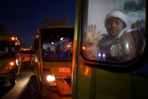 یک کودک مهاجر که بخشی از کاروان مهاجران آمریكای مرکزی است داخل یک اتوبوس در کلانشهر گوادالاخارا مکزیک نشسته است