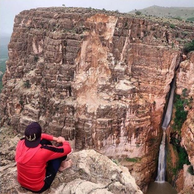گردشگر آمریکایی در کنار آبشار پیران در کرمانشاه