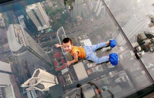 یک پسربچه بر روی پل شیشهای در شهر بانکوک تایلند