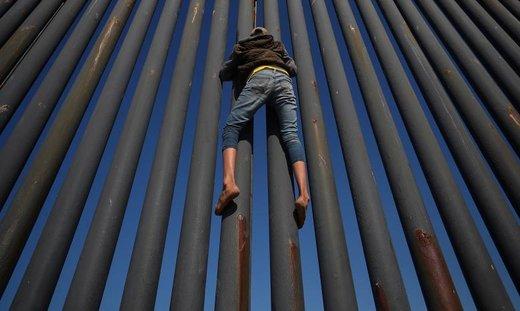 یک مهاجر از کاروان مهاجران آمریکای مرکزی از حصار مرز مکزیک و آمریکا بالا میرود