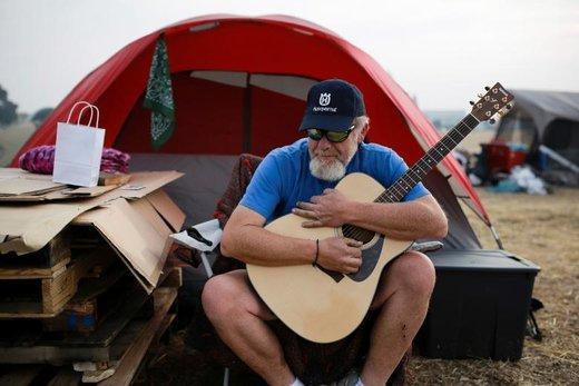 یکی از ساکنان شهر پارادایس کالیفرنیا که در آتش سوزی خانه اش را از دست داده در کنار چادرش گیتار می نوازد