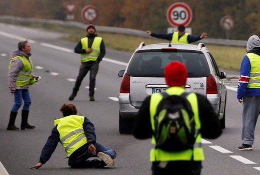 محاصره یک خودرو توسط معترضین با جلیقه های زرد در فرانسه. آنها نماد اعتراض رانندگان فرانسوی به قیمت بالای سوخت هستند