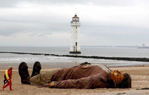 مامور نجات غریق مقابل یک عروسک در سواحل New Brighton بریتانیا