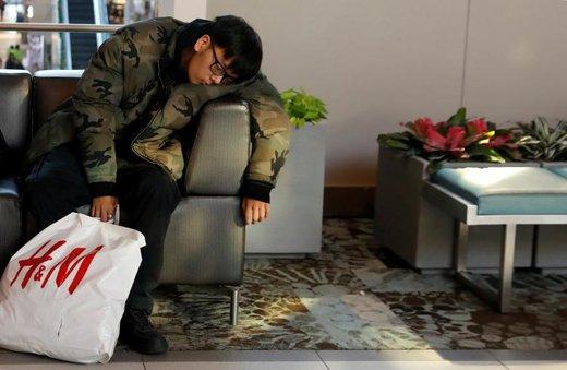 یک فرد در خرید جمعه سیاه در بازار روزولت فیلد در منطقه گاردن سیتی شهر نیویورک آمریکا خوابیده است