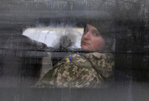 یکی از زندانیان سیاسی اوکراین و خدمه کشتی که توسط سرویس امنیتی روسیه بازداشت شده از پنجره مینی بوس خارج از ساختمان یک دادگاه در شهر سیمفروپول پایتخت جمهوری خودمختار کریمه در روسیه به بیرون نگاه می کند