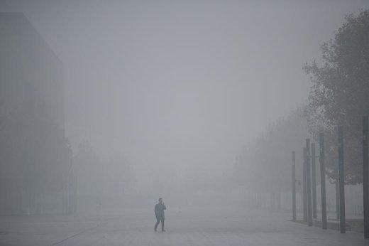 یک مرد در مه غلیظ شهر تیانجین چین از تلفن همراهش استفاده میکند. هشدار زرد آلودگی هوا در این شهر اعلام شده است