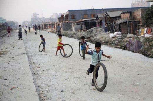 بچه ها با لاستیک در خیابانی در شهر داکا، پایتخت بنگلادش بازی میکنند