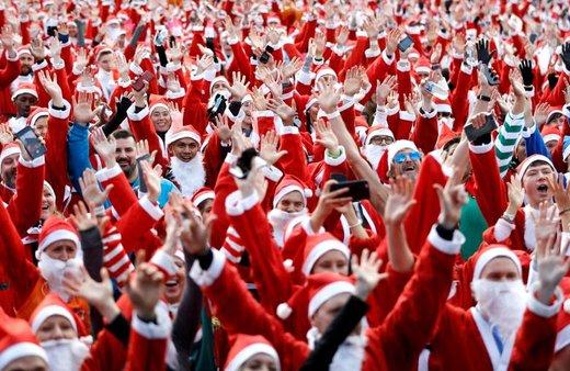 پیش از آغاز مسابقه دوی بابانوئل ها در لندن، رقبا خود را گرم می کنند. این رقابت دوم دسامبر در ویکتوریا پارک برگزار شد