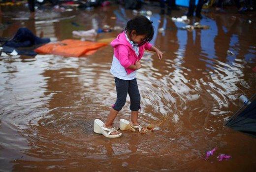 دختر 4 ساله هندوراسی که با کاروان مهاجران آمریکای مرکزی در یک پناهگاه موقت زندگی می کند کفشهای مادرش را پوشیده و در آبی که بعد از باران در نزدیکی پناهگاه جمع شده راه می رود