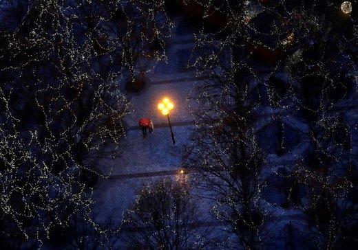 مردم در زیر درختان تزئین شده با چراغهای کریسمس در میدان قدیمی شهر پراگ، پایتخت جمهوری چک، قدم میزنند