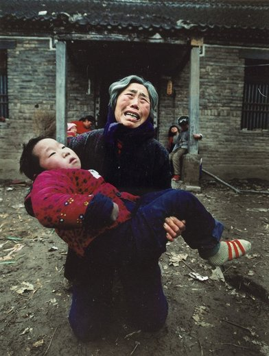 یک زن که نوه بیمارش را در آغوش گرفته برای سلامتی او به درگاه خداوند دعا می کند