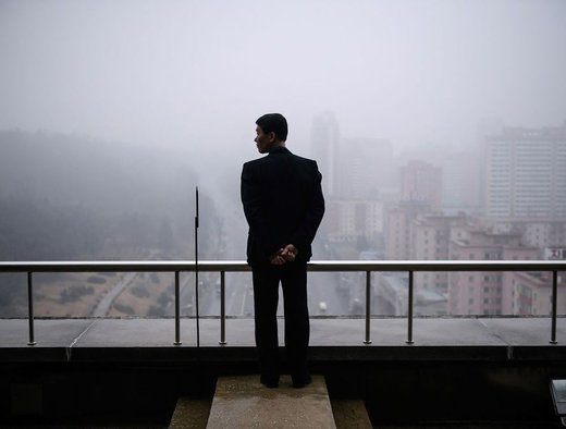 یک مرد در رصدخانه Arc de Triomphe در شهر پیونگیانگ ایستاده است