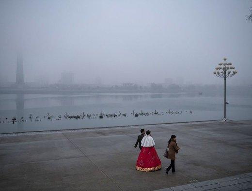 عروس و داماد در یک روز مه آلود در شهر پیونگیانگ