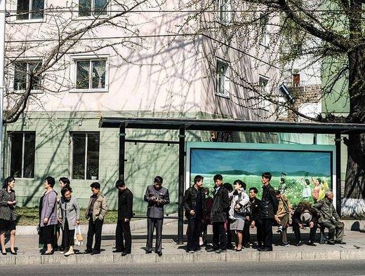 مسافران در ایستگاه اتوبوس شهر پیونگیانگ  منتظر اتوبوس هستند