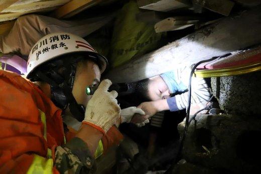 یک آتش نشان به پسربچهای که پس از وقوع زلزله در استان سیچوان چین زیر آوار مانده، کمک میکند تا نجات پیدا کند