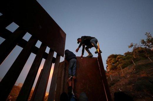 تلاش یک مهاجر هندوراسی برای عبور از مرز آمریکا در شهر تیخوانا مکزیک