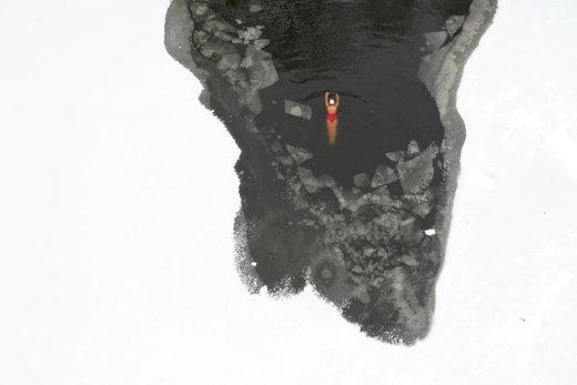 یک شناگر زمستانی در یک رودخانه یخ زده در شهر شنیانگ چین شنا میکند