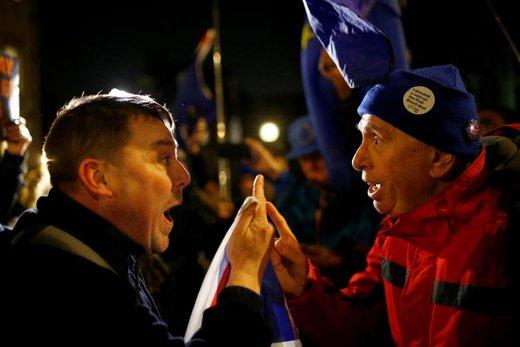 دو تظاهر کننده در مقابل پارلمان لندن در وستمینستر