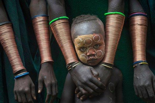 یک پسر قبیله سوری که در دره Ethiopia's Omo اتیوپی زندگی می کند همراه زنان این قبیله است که دارای النگوهای مسی هستند
