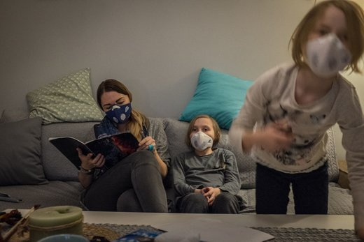 یک شهروند در شهر کراکوف لهستان با دو فرزندش هنگامی که پنجره خانه را باز می کنند یا از خانهشان خارج می شوند از ماسک استفاده میکنند