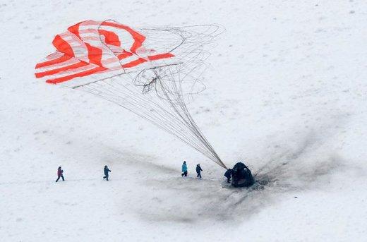 تیم جستجو و نجات به فضاپیمای سایوز نزدیک می شود که در یک منطقه دورافتاده در قزاقستان فرود آمده است
