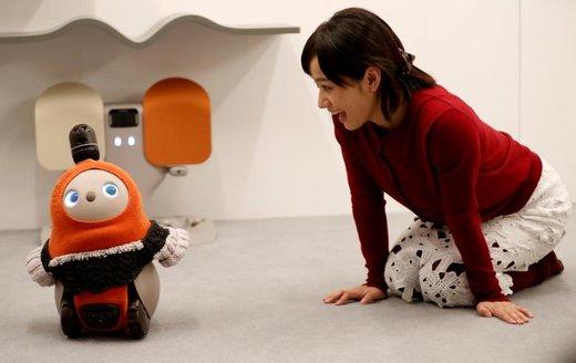 زنی در حال فراخواندن یک ربات خانگی در نمایشگاه رباتها در شهر توکیوی ژاپن است