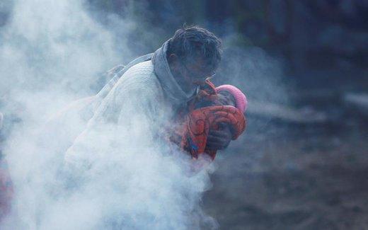 مردی در سرمای شدید دهلی نو، کودکش را در پتو پیچیده و در کنار آتش سر می کند