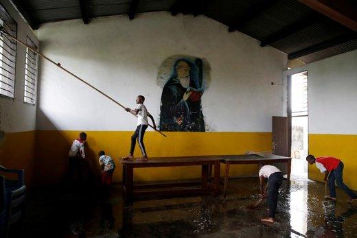 پسران به تمیز کردن یک کلیسا برای آماده سازی جشن کریسمس در شهر کینشاسا کنگو کمک میکنند