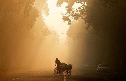 یک مرد در هوای مهآلود شهر دهلینو هند سوار ریکشا شده است