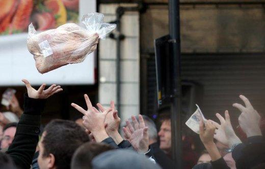 خریداران گوشت در یک حراج کریسمس در بازار Smithfield شهر لندن انگلستان