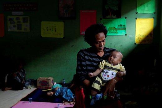 یک مرد تحت تاثیر سونامی در استان بانتن اندونزی یک کودک را درون مدرسهای که از آن به عنوان پناهگاه استفاده میشود، نگه میدارد