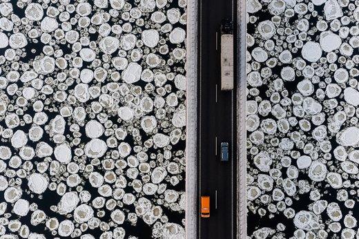 یک کامیون و اتومبیل در جاده قدیمی نزدیک رودخانه پوشیده از یخ Vistula  لهستان حرکت میکنند