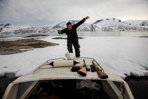 یک شکارچی در پشت قایقش در شهر Tasiilaq گرینلند