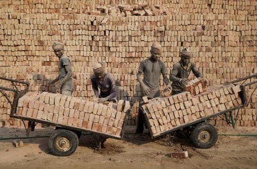 کارگران کارخانه آجرپزی، آجرها را روی ارابهها در شهر داکا بنگلادش قرار می دهند