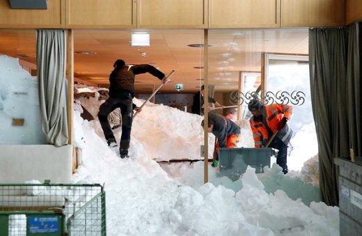 در پی ریزش بهمن در سوئیس کارگران تلاش می کنند تا رستورانی را که زیر برف مانده، پاکسازی کنند