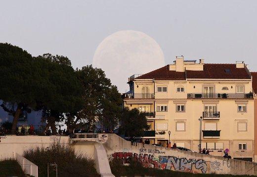 مردم غروب خورشید را در شهر لیسبون پایتخت پرتغال تماشا میکنند در حالیکه ماه کامل پشت آنها است