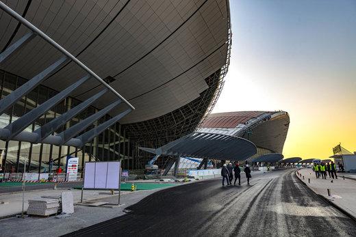 کارگران در 19 دسامبر سال 2018 در خارج از فرودگاه بینالمللی داشینگ پکن راه میروند