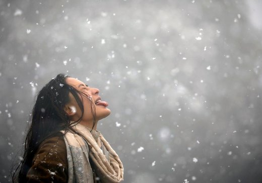 یک زن سعی می کند در زمان بارش برف در Chandragiri Hills واقع در شهر کاتماندو نپال،  برفها را با زبانش بگیرد