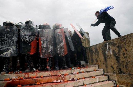 نزدیک شدن یک معترض به افسران پلیس در تظاهراتی در اعتراض به تغییر نام مقدونیه در شهر آتن یونان