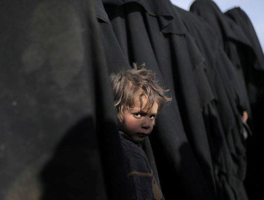 یک پسربچه در نزدیکی استان دیرالزور سوریه به دوربین نگاه می کند