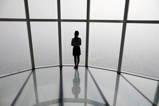 یک زن به شهر سئول کره جنوبی نگاه می کند که مملو از گرد و غبار است