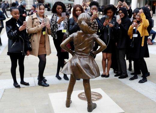 """دانش آموزان برخی از مدارس دخترانه لندن از مجسمه """"دختر بیپروا"""" که در خیابان به نمایش گذاشته شده، عکس میگیرند"""