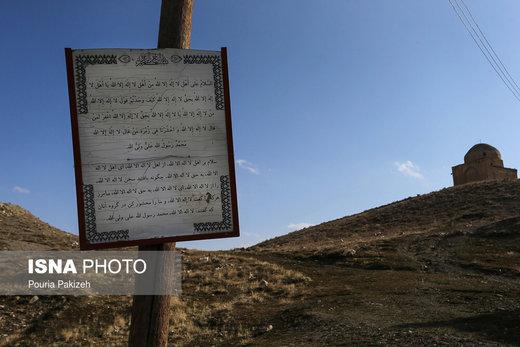 زیارت نامه نصب شده در ابتدای قبرستانی قدیمی که در وسط روستای «ازناو» و امامزادهگان «عین و غین» قرار گرفته است