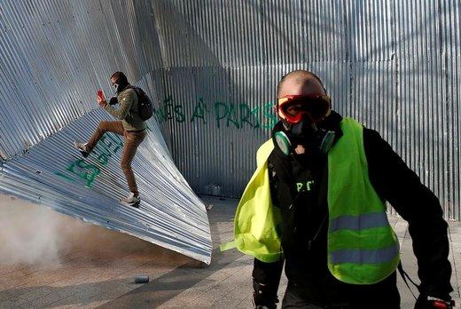 در تظاهرات جلیقه زردها در شهر پاریس فرانسه، یک معترض در مقابل دیوار فلزی تخریب شده، راه میرود