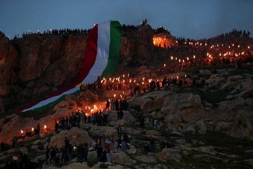 مردم کردستان عراق در  مراسم جشن باستانی نوروز در شهر عقره، مشعلی را تا بالای کوه حمل میکنند