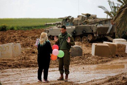 زنی در بخش اسرائیلی نوار غزه به یک سرباز اسرائیلی بادکنک هدیه می دهد