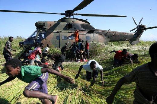 مردم سیلزده موزامبیک پس از دریافت کمکهای غذایی از هلیکوپتر امدادی آفریقای جنوبی دور میشوند