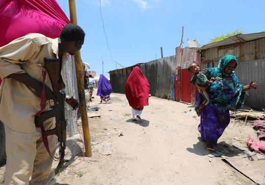 سرباز سومالی پس از حمله انتحاری گروه افراطی الشباب به ساختمان دولتی در شهر موگادیشو سومالی از محل نگهبانی می کند