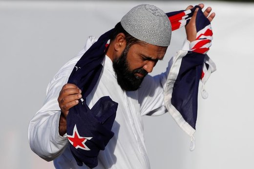 مردی در مراسم خاکسپاری قربانیان حملات مساجد، در شهر کرایستچرچ نیوزیلند پرچم این کشور را در دستانش گرفته است